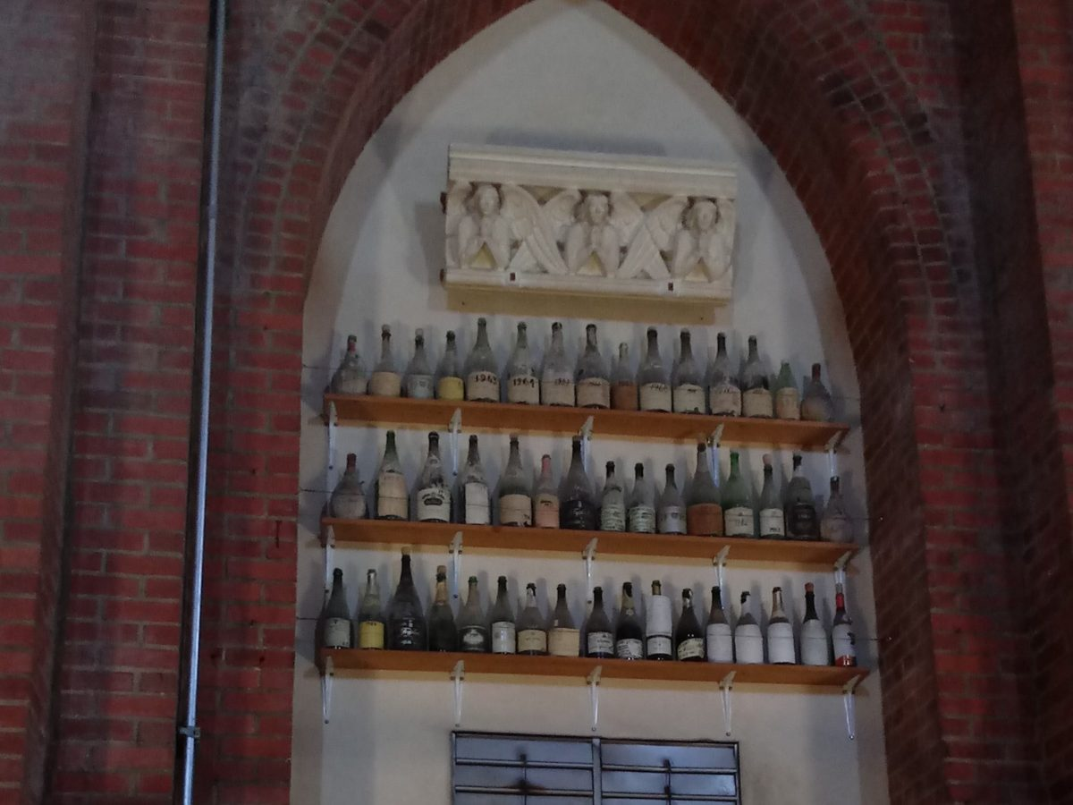 Far above the altar, this collection of wine bottles is signed and dated by the artisans