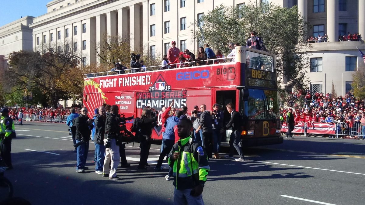 Ryan Zimmerman stands on the last bus as the World Series trophy is shown up close to the crowd
