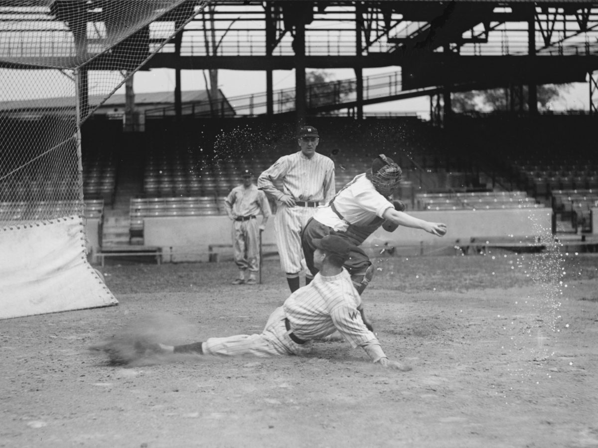 The catcher, a woman, throws to a base as a Senators play slides in at the plate