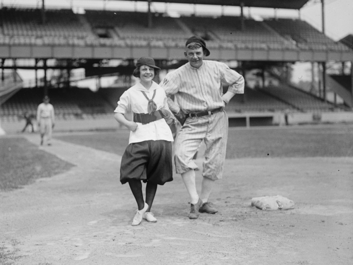 Washington Senators coach Nick Altrock poses with a woman baseball player near first base