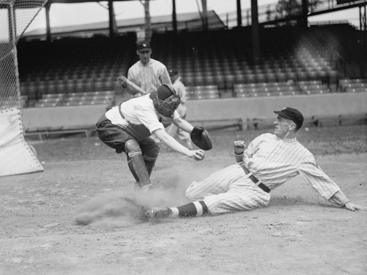 A Washington Senators player (Bucky Harris?) slides in at the plate as the catcher, a woman, applies the tag