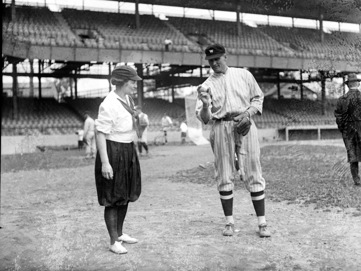 Walter Johnson demonstrates his pitching grip to one of the women baseball players