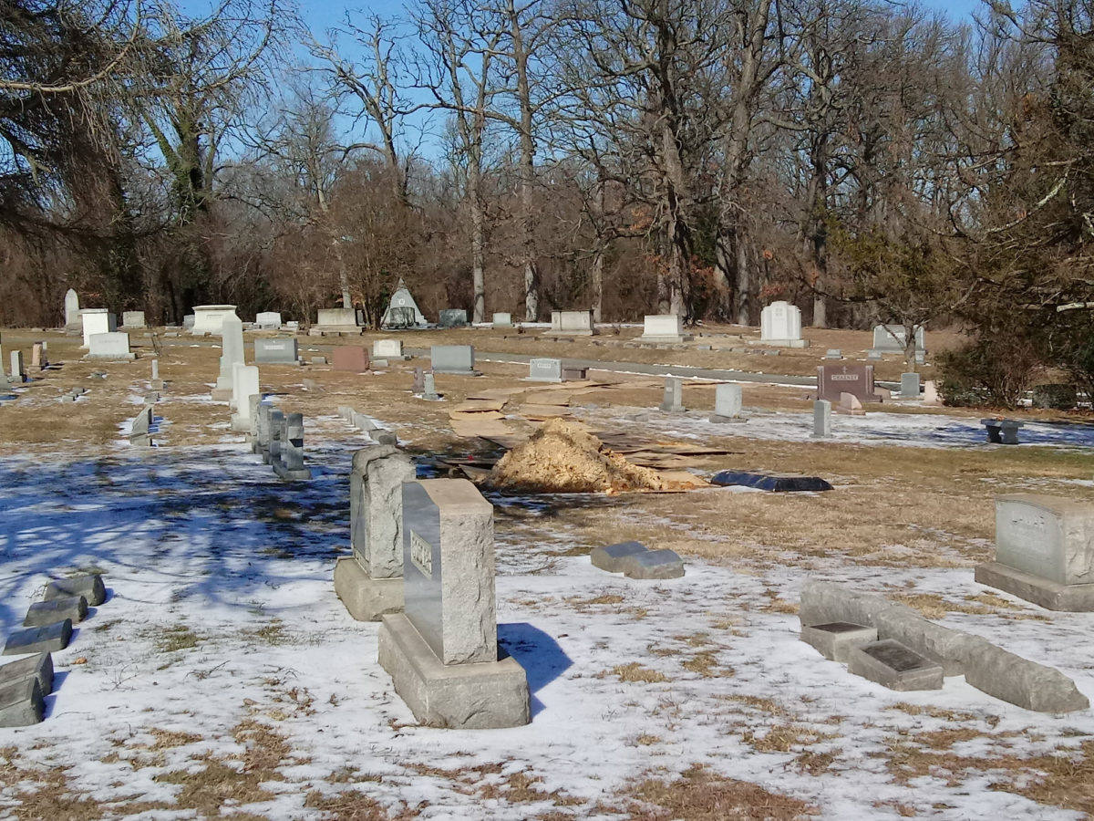 A pile of dirt, and lid of a burial vault, and planking at Loudon Park