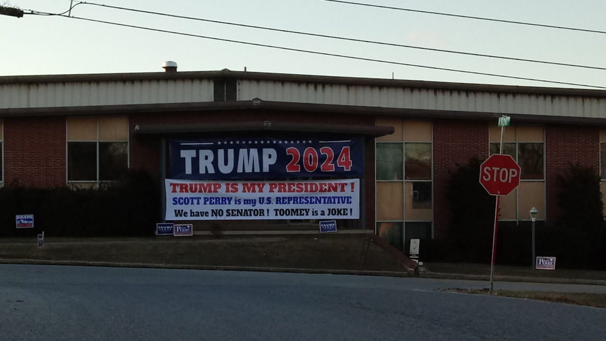 A massive Trump 2024 banner in front of a local business