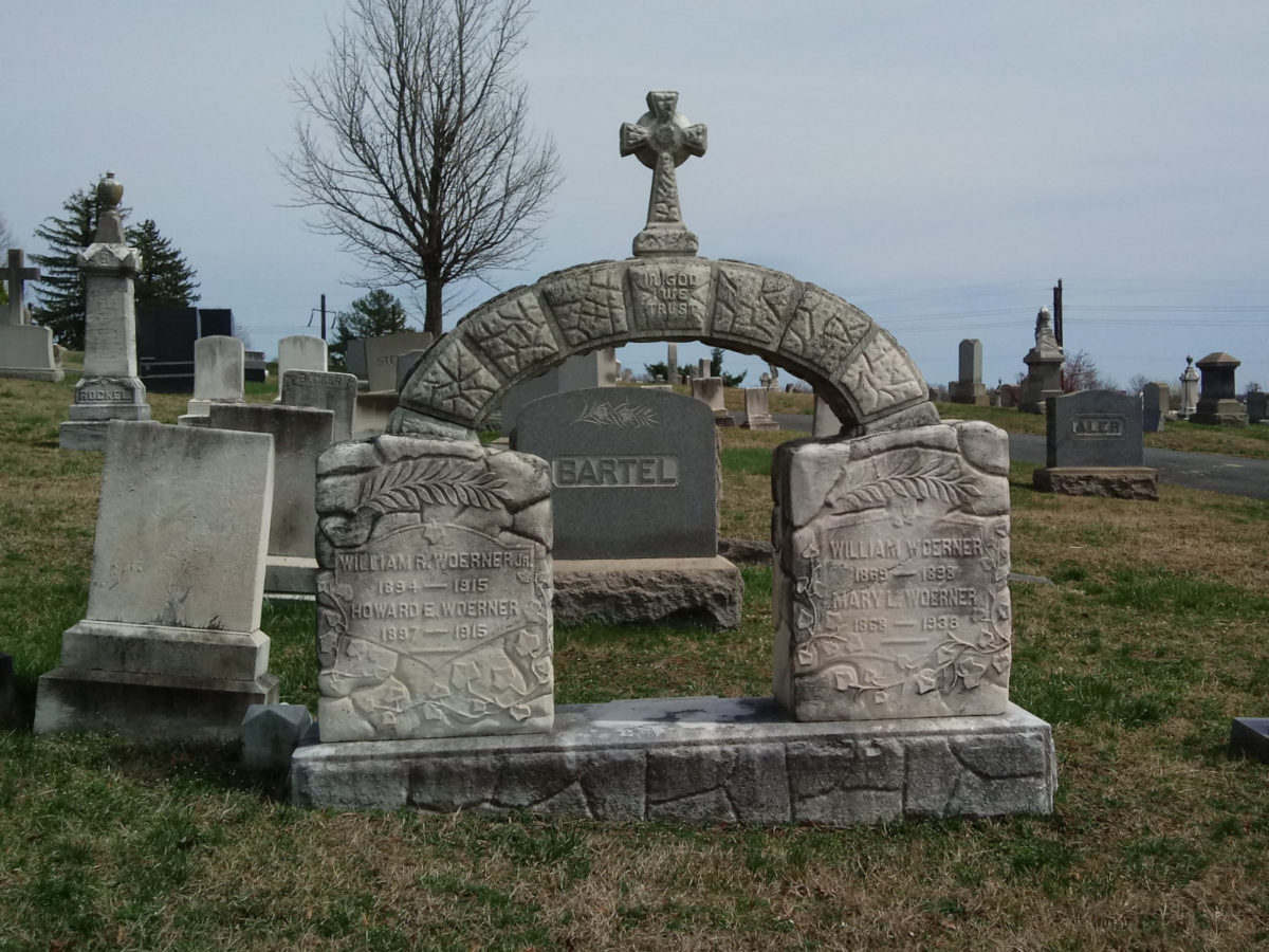 An elaborate memorial of two headstones topped by an arch topped by a Celtic cross