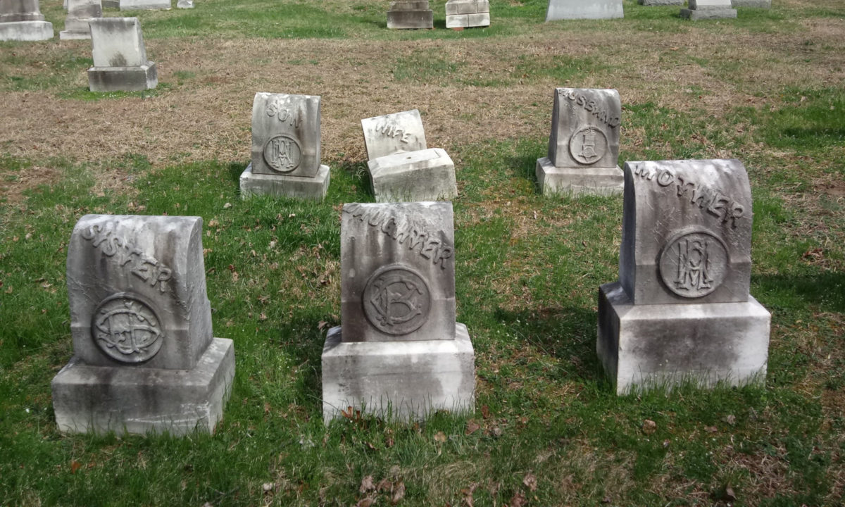 A group of headstones with elaborate relief carvings and old-style, turn-of-the-century typography
